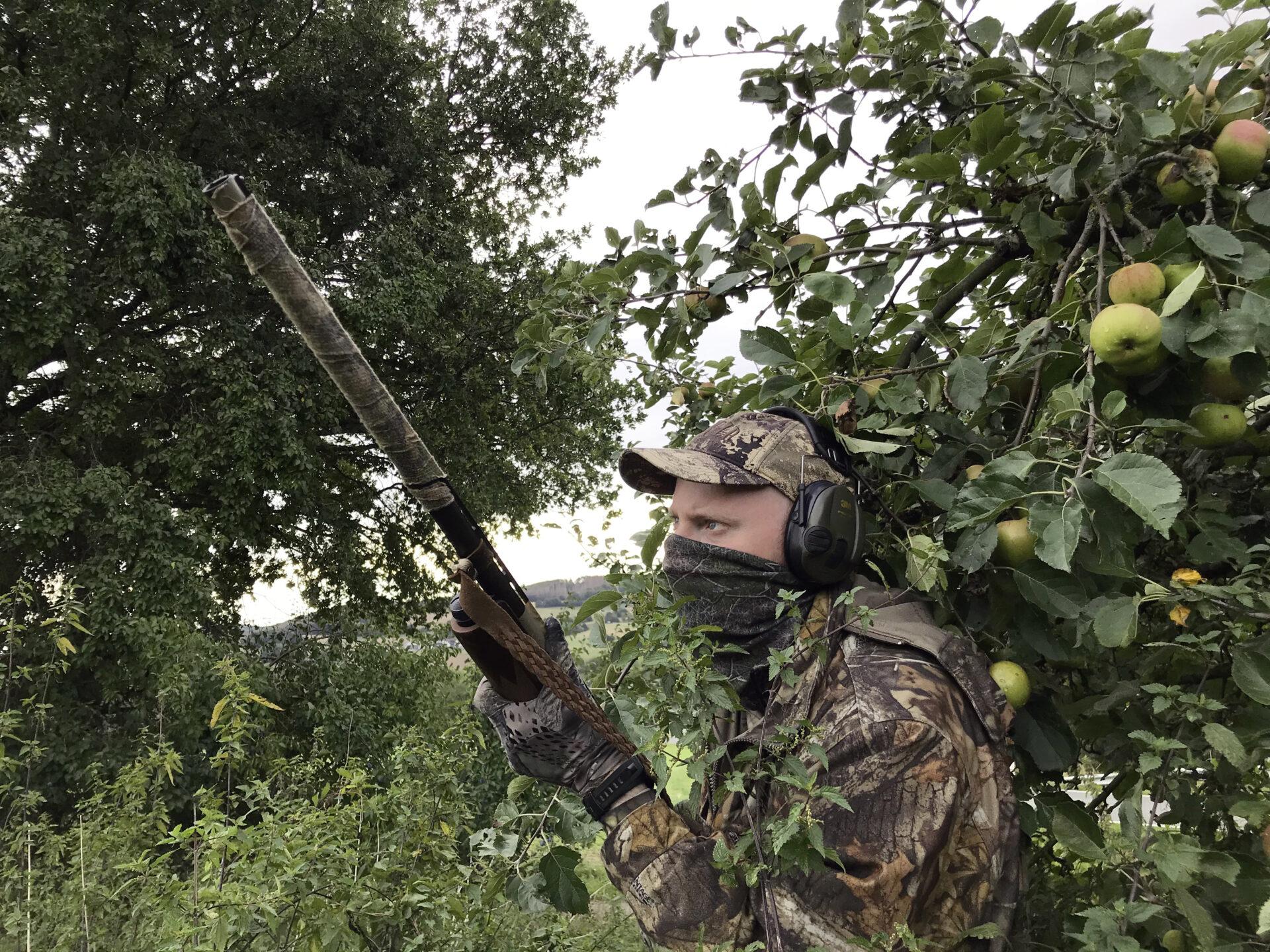 Ein getarnter Jäger bei der Elsternjagd