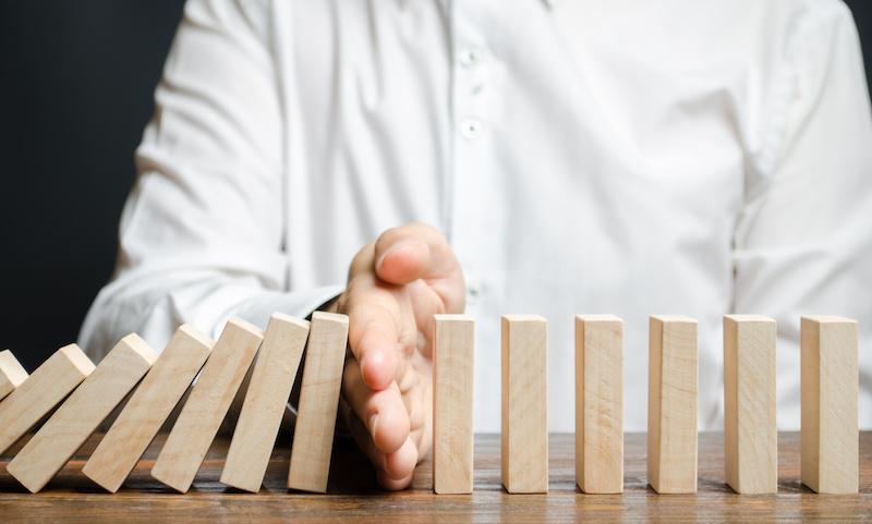 Hand zwischen Dominosteinen als Zeichen für Umstrukturierung